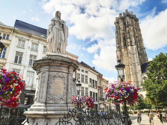 Escultura de Margarita de Austria con la Torre de la Catedral de San Rumoldo al fondo. Mechelen.
